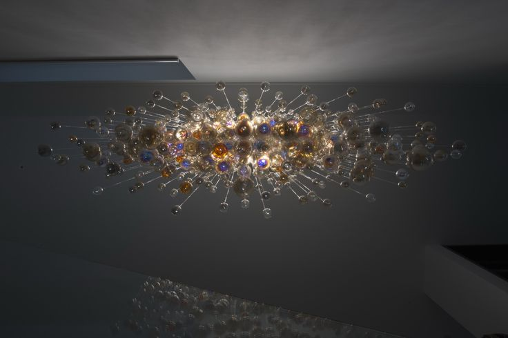 Modern chandelier made of hand blown glass hanging on sparkling fiber optics. Individual lighting project solution.
