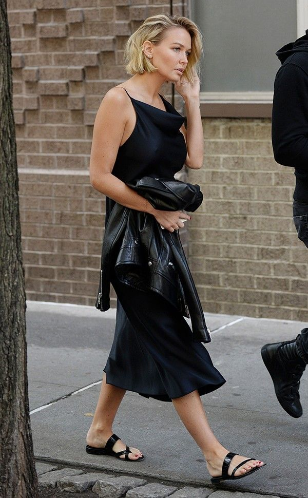Lara Worthington wears a black slip dress, leather jacket and slides