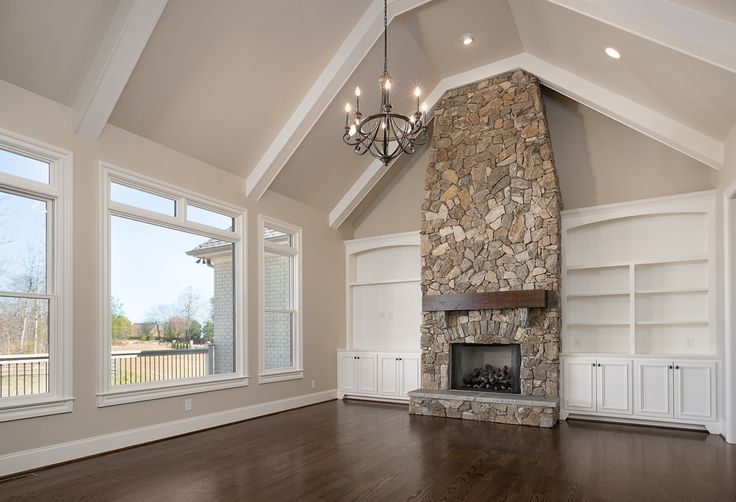 The perfect living room. Vaulted ceilings and an iron chandelier, floor to ceiling stone fireplace with farmhouse style mantle, custom built shelves on either side and the prettiest hardwood floors!  This gorgeous home in Greenville, SC is for sale! See and read more here - http://www.goodwinfoust.com/homesforsale/