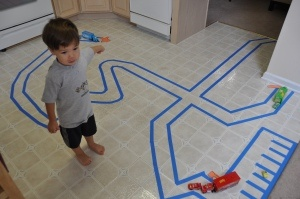 A homemade highway using painter's tape. Might be fun to try hopscotch like this as well!
