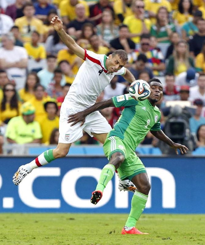 Iran's Jalal Hosseini heads the ball past Nigeria's Emmanuel Emenike during the group F World Cup soccer match between Iran and Nigeria at t...