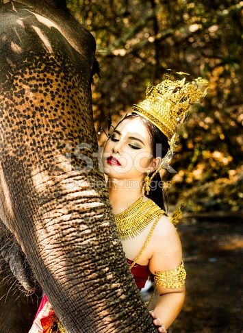 Tradtionally dressed Thai model close up with an elephant.