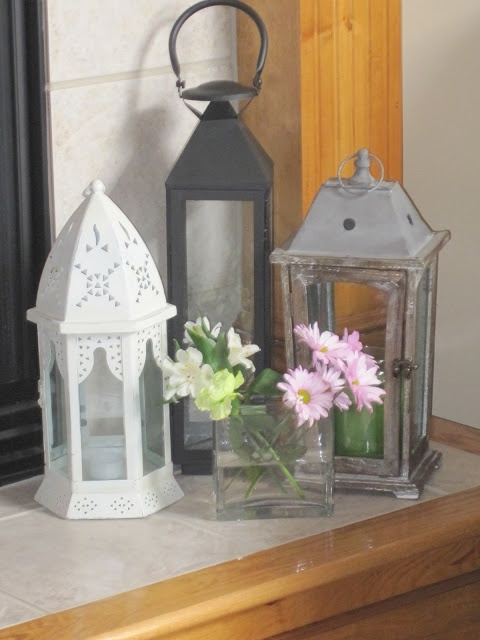 Display of lanterns on the fireplace hearth.