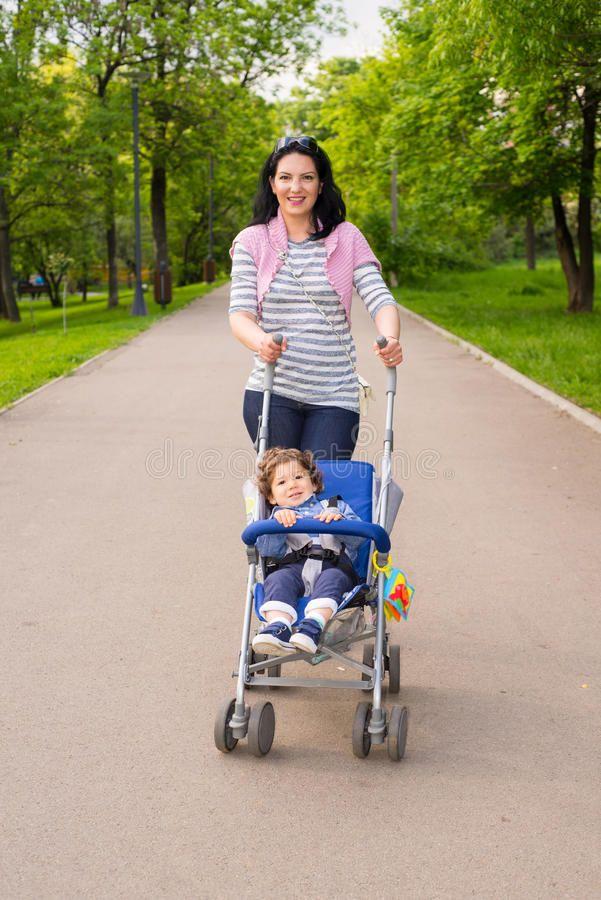 Happy Mom Pushing Pram With Toddler In Park Stock.  baby  pram  mom ... 97f844c13c