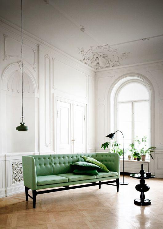 modern slender tufted sofa, black sculptural table & lighting, plants in humble terra cotta