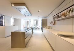 Moderne witte keuken met groot eiland. Deze prachtige keuken is de bulthaup b3. Door de strakke vormen en witte kleur is deze keuken een echte moderne blikvanger in elk huis. De dubbele afzuigkap is aan het plafond gemonteerd. Deze bevat bovendien een aantal handige spotjes waardoor je altijd genoeg licht op de kookplaat hebt. Aan de wand bevindt zich een plank voor de kookboeken. Zo heb je altijd je favoriete recepten bij de hand.