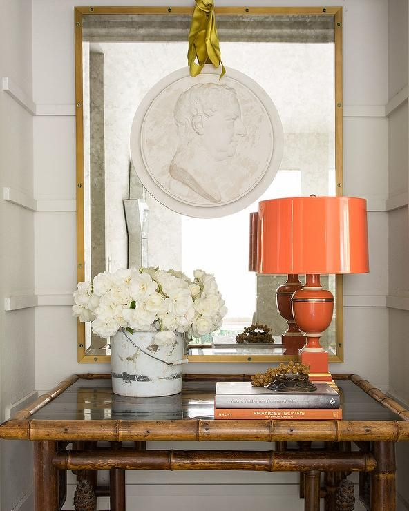 Eclectic foyer vignette with Mary McDonald orange lamp, bamboo table & large-scale medallion