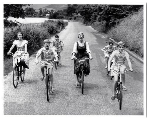 "Julie Andrews, Charmian Carr, Nicholas Hammond, Duane Chase, Angela Cartwright, Debbie Turner and Kym Karath ride bikes. And sing ""Do-Re-Mi.""    Tags: The Sound of Music bicycle Do-Re-Mi Robert Wise Twentieth Century Fox 1965 Julie Andrews"