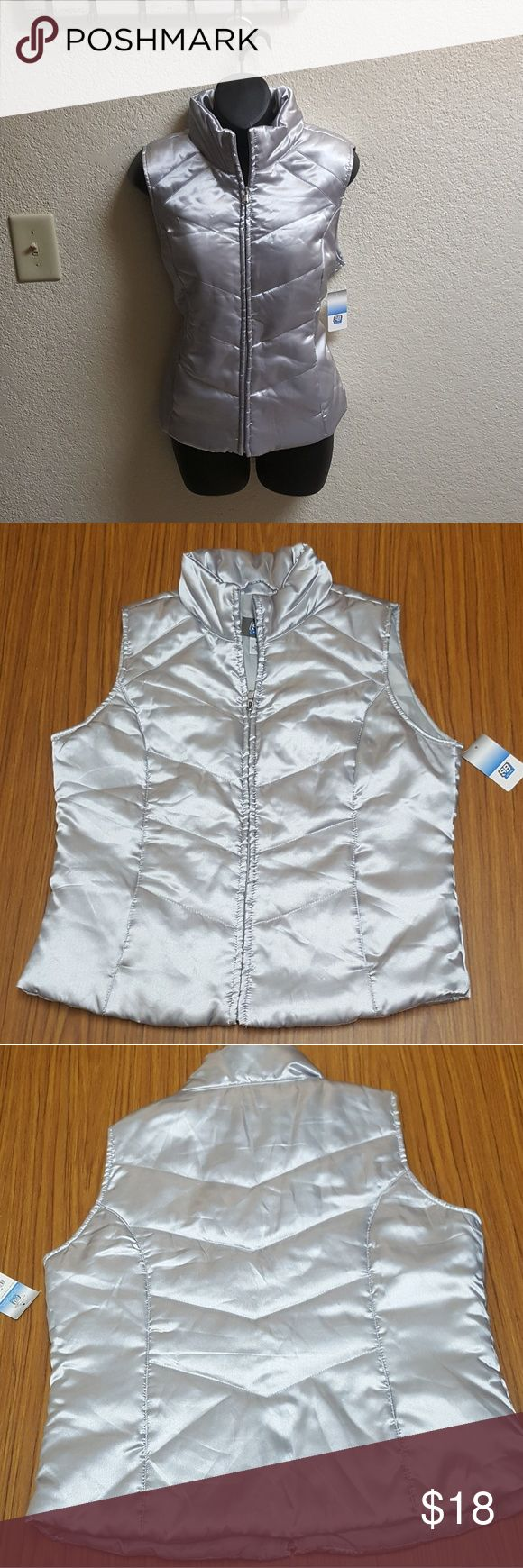 "SJB Active Silver Vest SJB Active Silver Vest. Size Medium. Has side pockets. New with tags. 100% Polyester shell, lining, and filling. Machine wash warm and tumble dry low.  Perfect for layering over a long-sleeve shirt and staying warm! *Bust 41"" *Length 23.5"" SJB Jackets & Coats Vests"