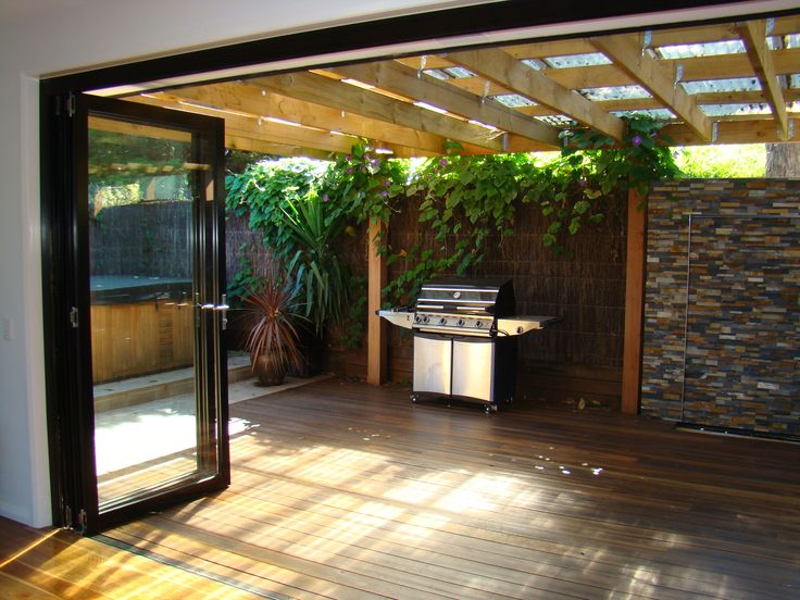 Sun room with bifold doors extending onto decking and outdoor entertainment area.. my dream so i can entertain often
