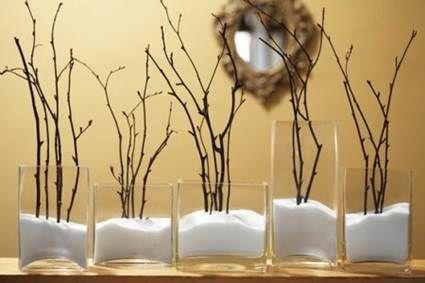 como hacer un fantástico centro de mesa con tan sólo un jarrón de cristal, sal gruesa y ramas de árbol secas.