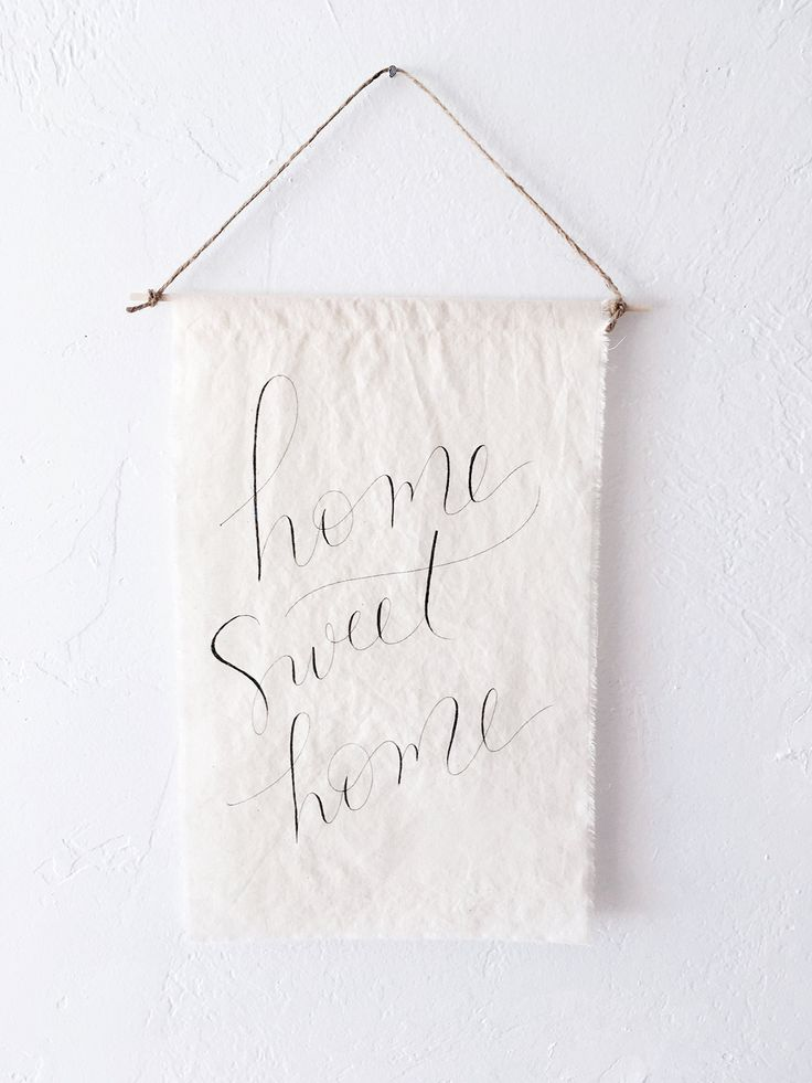 """FABRIC home sweet home sign, tapestry, textile art, housewarming, rustic, simple, modern, lettered, calligraphy, gift, home decor, farmhouse. A beautiful original piece of art. Hand lettered calligraphy on a lovely piece of natural fabric, with frayed edges. Fabric measures approximately 10""""x14.25"""". Finished with a wood dowel and twine. Note: Tapestries are decorative only and not waterproof. Please do not launder. Need a custom sign? Just message us! Copyright Sweetgrass Paper Company..."""
