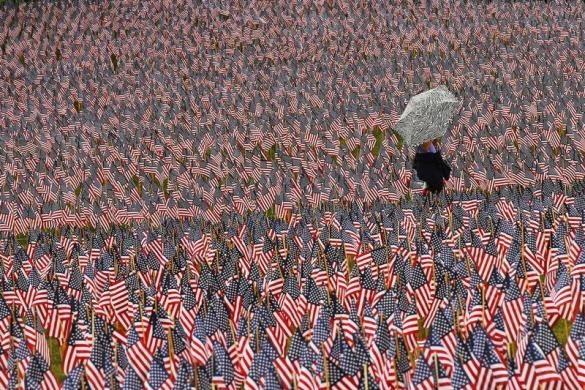 A pedestrian carrying an umbrella walks through a Memorial Day display of United States flags on the Boston Common in Boston, Massachusetts May 23, 2013. According to the Massachusetts Military Heroes Fund, the flags are planted on the Common for fallen Massachusetts service members at the Memorial Day holiday, which will be celebrated May 27 in the U.S. REUTERS-Brian Snyder