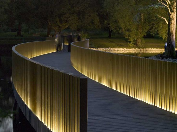 The Sackler Crossing, Kew Gardens. John Pawson Architects. The uplighting illuminates the bronze upstands on both sides of the bridge, creating a beautiful glowing structure which floats above the still water. The treads are made of granite.