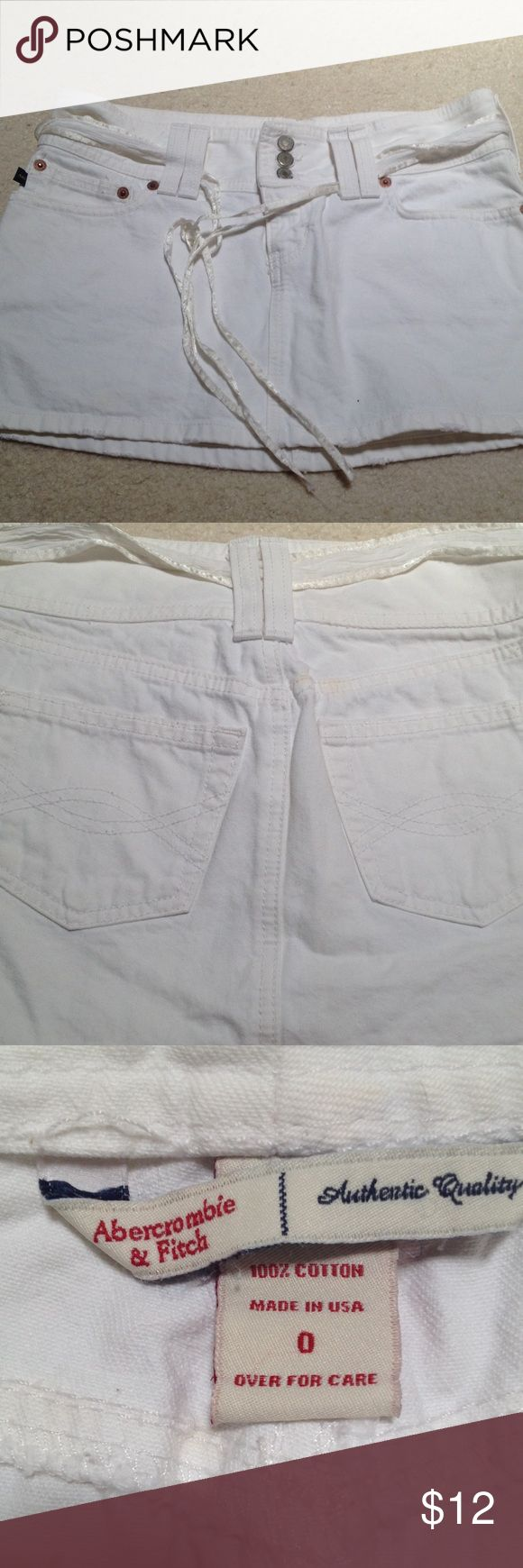 Abercrombie and Fitch white denim mini skirt sz 0 Abercrombie and Fitch white denim mini skirt sz 0 with tie detail. It has a slightly distressed hem (seen in last pic).  The second pic shows a slight stain above the right pocket. Not that noticeable but it's there. Abercrombie & Fitch Skirts Mini