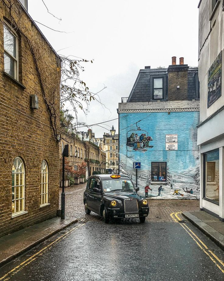 A mews street in London's South Kensington with a ski mural painted on it and a classic black cab.   #london #mews #taxi #southkensington #mural