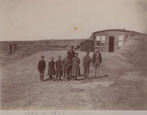 Dugout schoolhouse, Thomas County, Kansas - a group of students and their teacher standing before the District #67 dugout school between north and south Randall, Kansas on the east side of township 27-9-31, in Thomas County, Kansas. The school was established September 22, 1887 and the last term was taught in 1918-19. The school year was six months long and the teacher received $30.00 per month in wages.