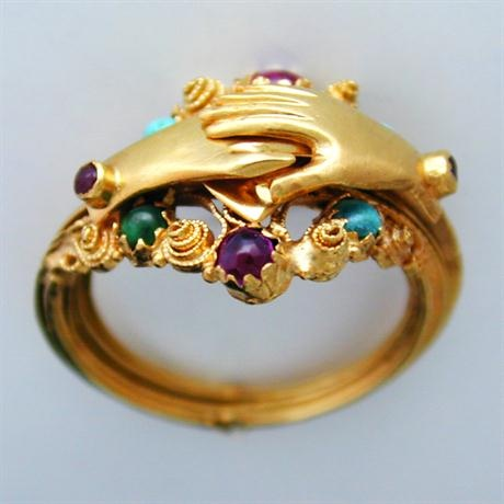 A Regency gemset gimmel ring, the triple yellow gold band connecting to form clasped hands over a heart, within a garnet and turquoise set cannetille work border, gross weight 4.8 grams, circa 1820.