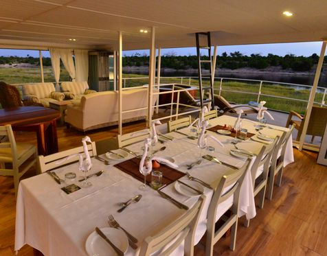After sipping on a traditional African safari sundowner, sit down to a three-course evening meal as you're serenaded to the sounds of elephant and perhaps even lion nearby. The perfect end to a magical day.  #ChobePrincess | #Houseboat | #RiverSafari