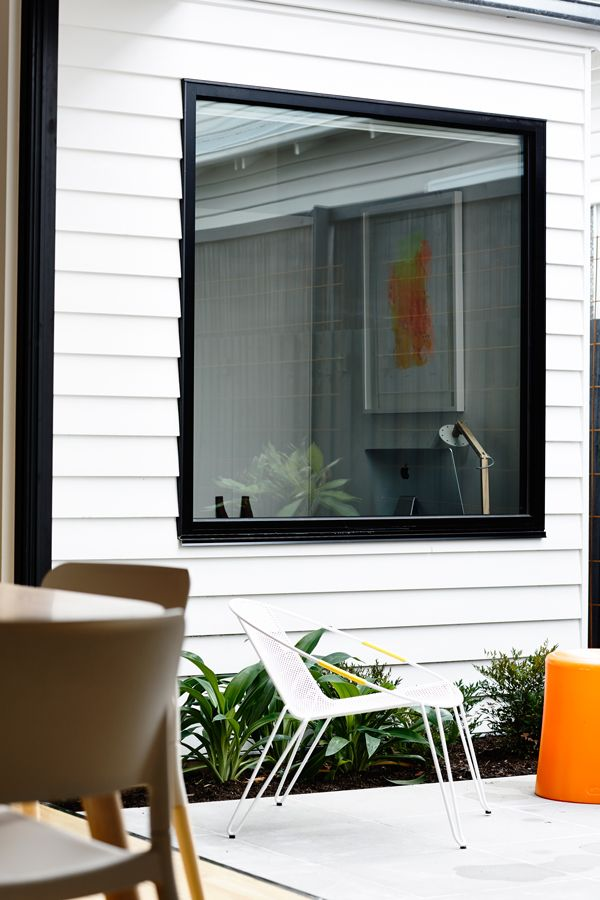 White weatherboard with black trim, window frame