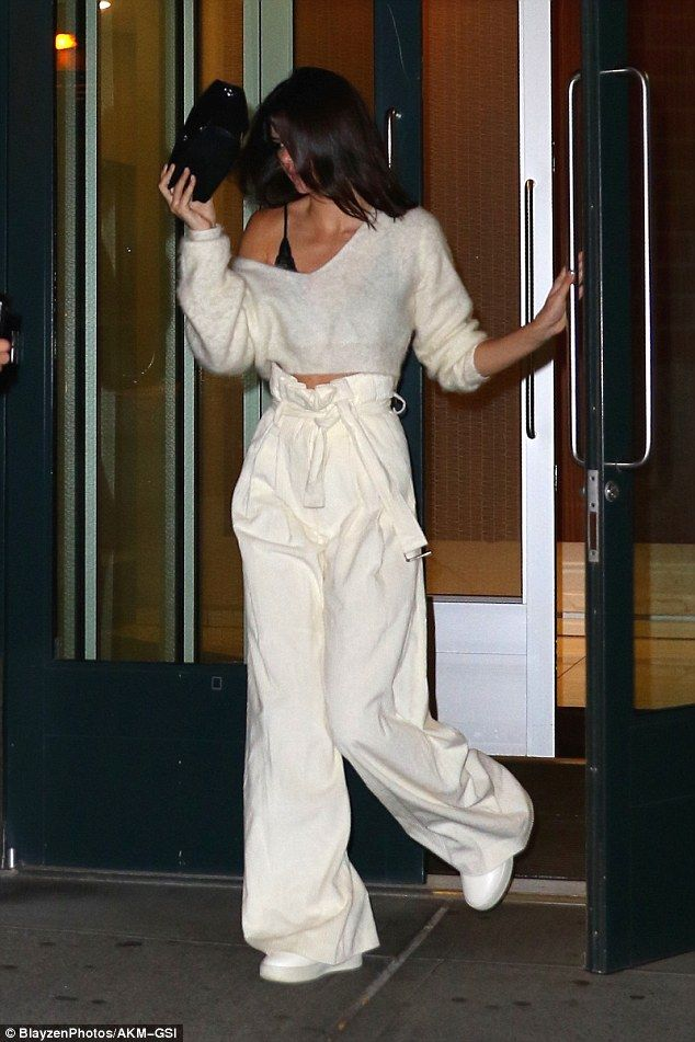 All white on the night: The model wore an all-white ensemble including a cropped off the shoulder sweater, oversized high-waisted pants and pristine white sneakers