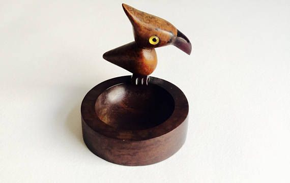 A charming characterful Bird made of Wood with a Phenolic Resin or Bakelite Beak and Feet in the form of an Ash Tray produced in the 1920s and marked with the YZ Trademark to the base.The Bird is in good vintage condition with some fine cracks to the Ash Tray being the only thing of note.7.5 Cms tall,6.5 Cms diameter,Weighs 50 Gms.