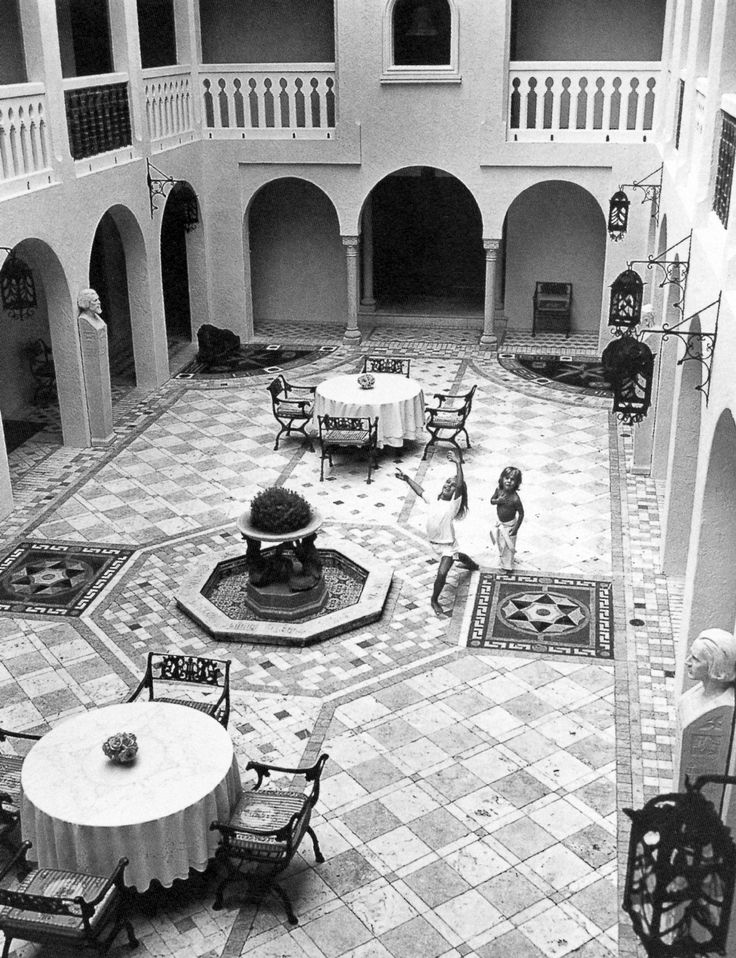 Allegra and Daniel [Beck] at play in the central courtyard with its original busts representing four of the continents. The elaborate tiled floor was designed by Sybil de Bourbon Parme and Janet Bussell. The Regency-style iron garden chairs feature Versace-print silk cushions.