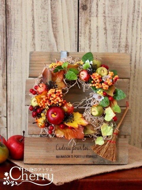 秋も深まってお庭の木々も色付き始めたら、いよいよ紅葉の季節。。実りの秋の可愛いミニリースの付いたスタンドをお部屋に飾りませんか??おまけに、お庭掃除用の可愛いホウキ付き!!この色を飾るだけで季節は秋本番ですね。こちらは置いても掛けても楽しめるお得で人気のアレンジです。『秋ハンドメイド2017』★ 作品サイズリーススタンド ・ 縦 21cm × 横 19cmリース ・ 直径 12cm★ 使用花材実付きアイビー・グリーンの葉っぱ・紅葉・白い小花・黒い小花・他(アーティフィシャルフラワー)赤青リンゴ・赤い実・カボチャ (フェイク)ミニホウキ1本ミニサンキライリース(ベースにソフトスパニッシュモスを巻いています。)★ その他リースはフックに掛けてあるように仕上げていますが、スタンドに直接ワイヤーで取り付けているので外れません。また、リーススタンドには元々傷や汚れが加工してありますのでご了解下さい。リースのベースに<ソフトスパニッシュモス>をゴールドワイヤーで巻き留めています、引っ張ると取れてしまいますのでご注意下さい。壁掛け用の紐をお付けして発送させて頂きます。