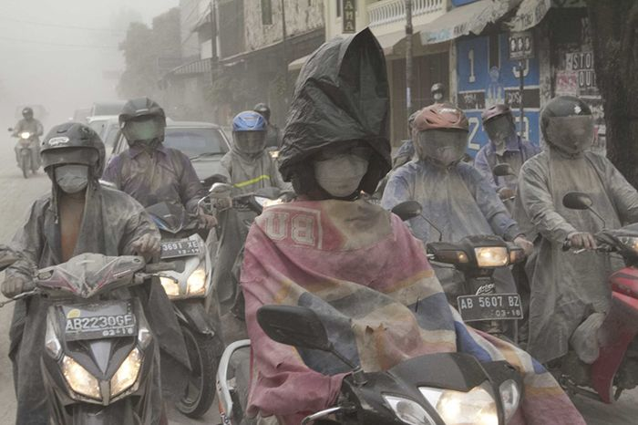 Tribun Jogja Photo/Hasan Sakri  A woman rides her motorcycle through the volcanic ashes of Kelud mountain, whilst wearing a plastic bag on her head in Yogyakarta - February 14, 2014.
