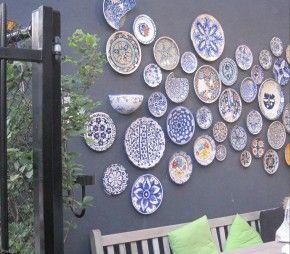 Muur met mediterrane bordjes. Leuk idee zeg om al die vrolijk gekleurde bordjes op te hangen aan de muur.