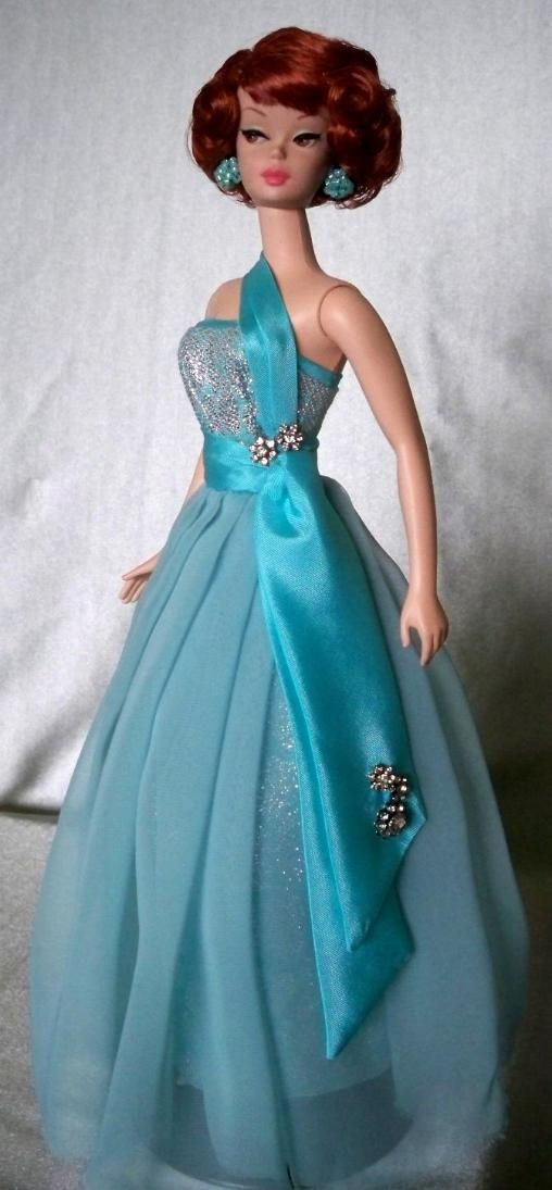 Barbie doll in a ball gown of aqua silk brocade with a floating layer of raw edged chiffon accented with a taffeta sash and Swarovski crystals.