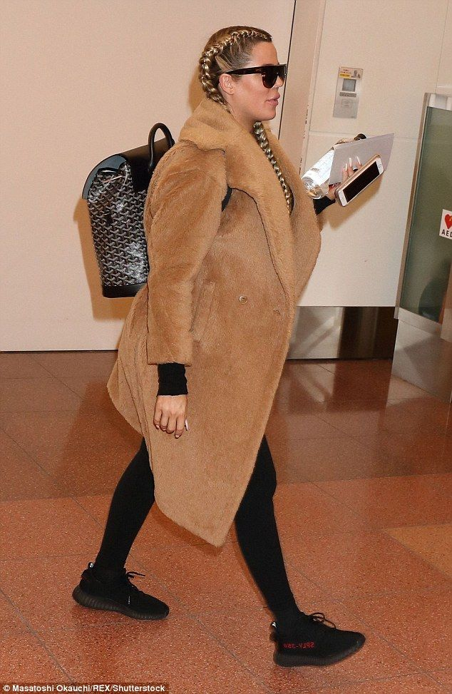 Bumping along:Khloe Kardashian shielded her baby bump in a chic faux-fur jacket as she touched down in Tokyo on Monday