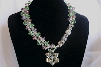 Unique asymmetrical intertwined design with translucent green and purple sparkling crystal and Rhinestone encrusted charms and a delightful rose pendant reminiscent of a bygone era.