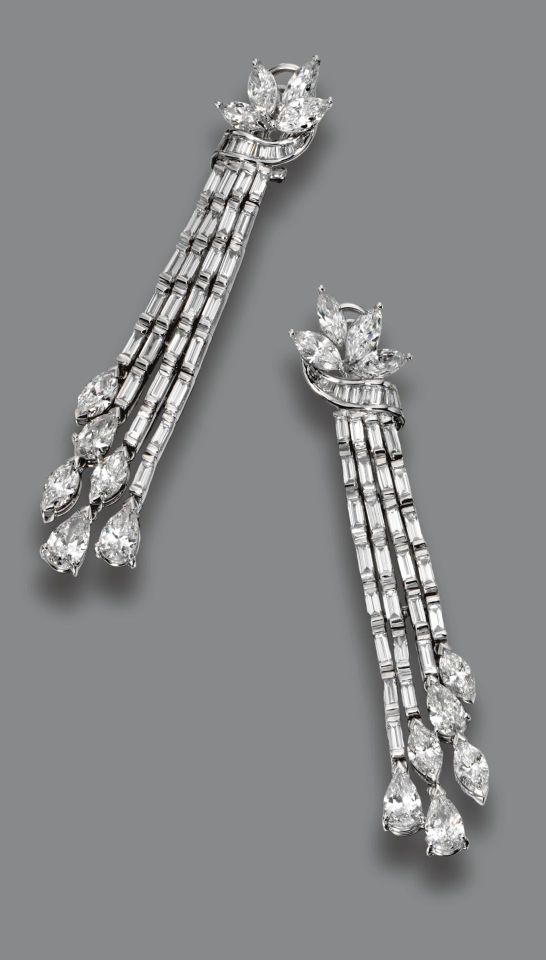 PAIR OF DIAMOND PENDANT-EARCLIPS. The tops designed as foliate clusters framed by a scrolling ribbon, supporting cascades of baguette diamonds anchored by pear-shaped and marquise-shaped diamonds, the whole set with 6 pear-shaped, 14 marquise-shaped and 72 baguette diamonds weighing a total of approximately 13.75 carats, mounted in platinum. Vintage or Vintage style, probably 1950s/early 1960s