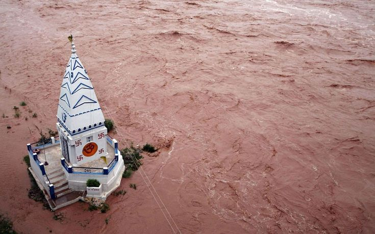 a temple stands amid the waters of the flooded river tawi after heavy rains in Jjammu, kashmir