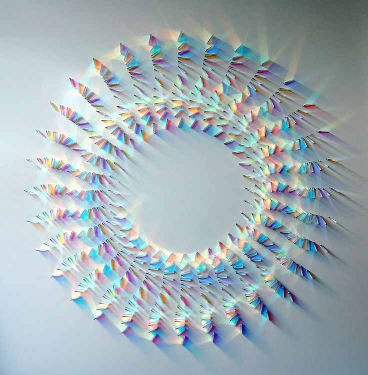Artist Chris Wood works with colored glass to create colorful, prism-like mazes and mandalas of light installed vertically on walls. Her most common material is dichroic (meaning 'two color') glass, a material invented by NASA in the 1950s that has a special optical coa