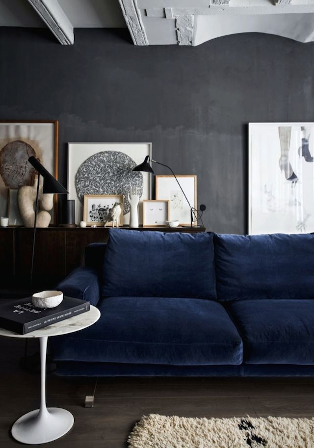 Dark navy velvet sofa against a dark