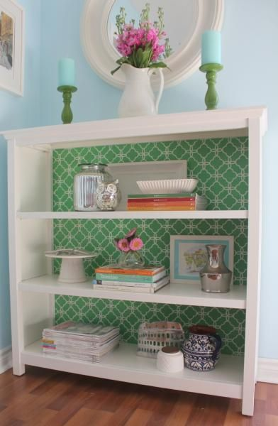 If you have a simple room and a neutral colored open bookshelf, to make the room more colorful, just cover the back of the shelf with a patterned fabric that ties in with the room's accent or wall color.