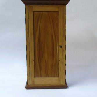 Pequeño armario realizado en madera de castaño de corte radial, con un panel frontal de un roble de 200 años y molduras de nogal americano. Las incrustaciones son de ébano y acebo. El tirador es de...