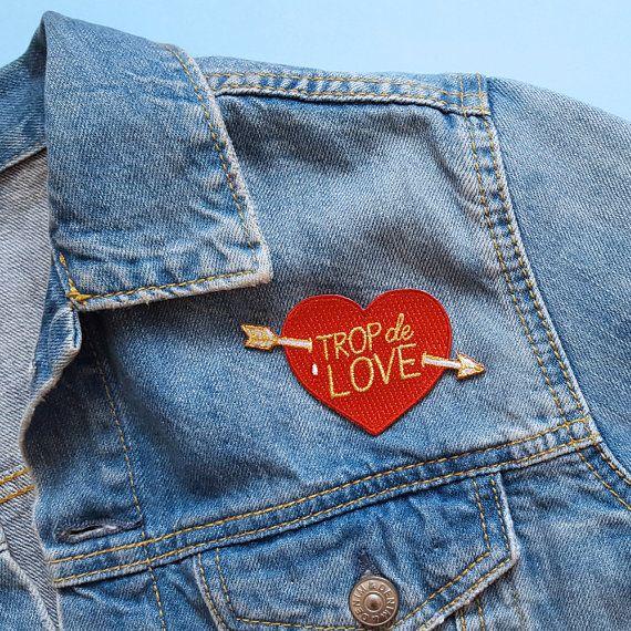Écusson brodé Trop de love  Vive le DIY, vive les patchs ! Customisez vos chemises, t-shirts, vestes, jeans, sacs avec ce patch thermocollant. Ce message damour personnalisera à merveille vos vêtements.  INFORMATION PRODUIT :  • Matériel : fil brodé, feutre et colle thermocollante. • Couleurs : rouge, blanc et or • Dimensions : 8 x 5 cm • Les patchs Trop de Love, sont emballés avec une carte dans une pochette plastique transparente, et envoyés dans une enveloppe à bulles et avec un numéro de…