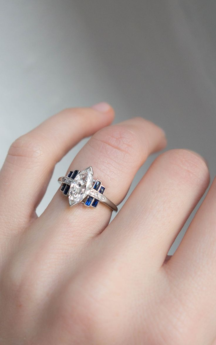 Vintage Art Deco engagement ring made in platinum and centered with a GIA certified 1.12 carat marquise cut diamond with H color and VS1 clarity. Accented with sapphires. Circa 1925