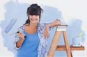 Woman holding paint roller leaning on ladder - Stock Photo