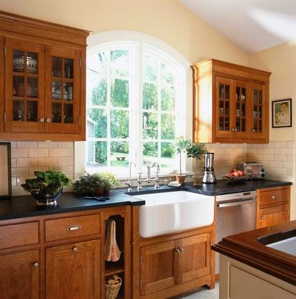 Soapstone counters + buttery walls + a classic farmhouse sink + subway tile backsplash + cherry cabinets + that gorgeous window = charming kitchen.