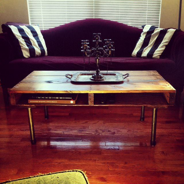 A coffee table made out of a recycled wooden pallet and metal plumbing pipes for the foot.
