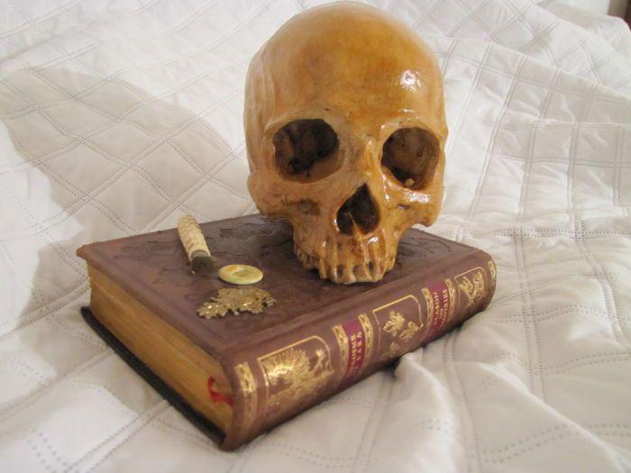 """Vanité Memento mori """"noblesse oblige"""" door Ried Gould  Vanité mémento mori """"noblesse oblige"""" door Ried Gouldkunstenaar freelance ontwerper.Deze ijdelheid is gemaakt van gemengde samenstelling en 1/1 (fullsize).Het bestaat uit een schedel in hars van zeer hoge kwaliteit hyper-realistische detailsdie werd geveegd en gelakt het een authentieke en oude uiterlijk geven.Het is gefixeerd op een semi-oude gebonden boek in leer en gesteld op vier voeten van brons gemaaktdie hebben ook een zegel van…"""