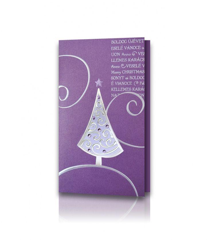 Kartka świąteczna B 514: Papier perłowy koloru fioletowego z drobinkami mieniącego się srebra. Choinka na froncie nabita srebrną folią z fioletowymi, mieniącymi się elementami - imitującymi bombki . Z boku widnieje srebrny napis Wesołych Świąt w różnych językach.