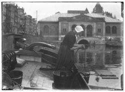 Een vrouw haalt water uit de Geldersekade voor het schoonmaken van het dek van een binnenvaartschip. Links vaste brug nummer 297 over Recht Boomssloot. Op de achtergrond de Vischhal.