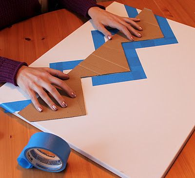She used an old piece of cardboard to measure & cut out a stencil in the chevron pattern.  As she held the stencil in place, husband took the painters tape and marked off where the stripes would be.  Getting the lines perfectly centered & evenly spaced was the hardest part...