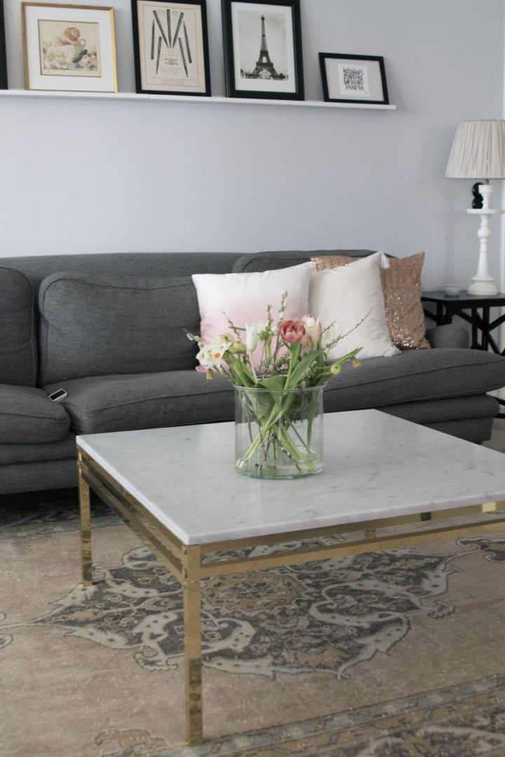 Grey sofa, marble table. Pretty rug.