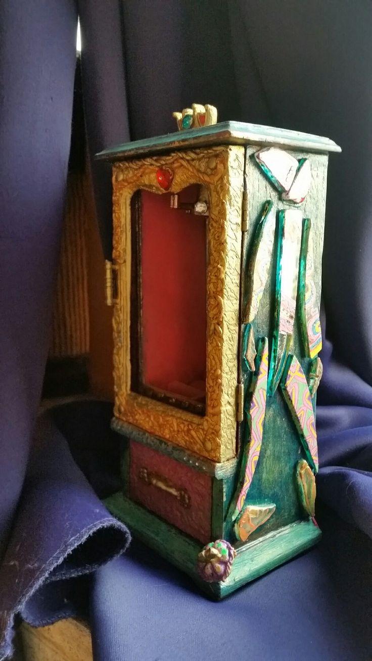 De zijkant bestaat uit willekeurige stukjes gebroken spiegel die ik beschilder.